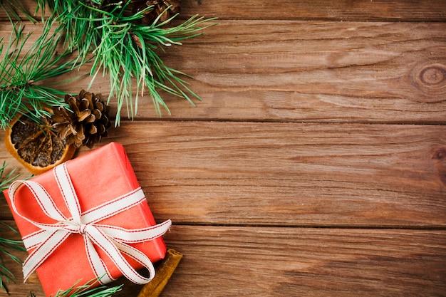 Weihnachtszweige und roter kasten auf hölzernem schreibtisch Kostenlose Fotos