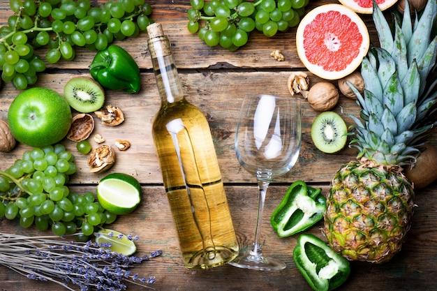 Wein-konzept. flasche und glas junger weißer biowein mit grünen trauben, pampelmuse und anderer frucht auf einem alten holztisch Premium Fotos