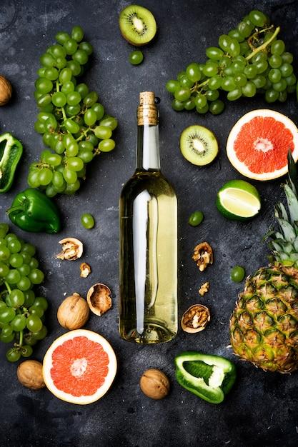 Wein-konzept. flasche und glas junger weißer biowein mit grünen trauben, pampelmuse und anderer frucht auf einem grauen steinhintergrund Premium Fotos