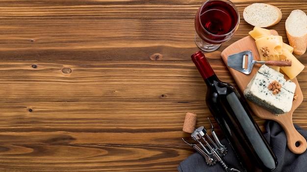 Wein mit lebensmittel auf hölzernem hintergrund Premium Fotos