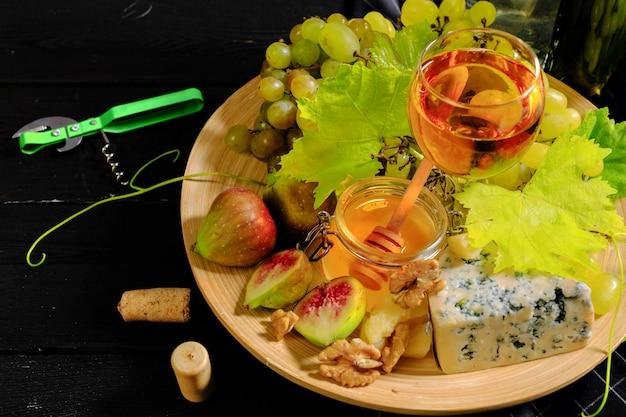 Wein mit zweigen der weißen trauben. auf einem holztisch. Premium Fotos