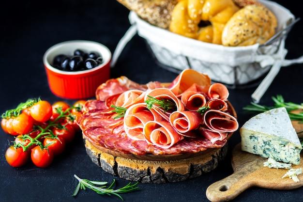 Weinaperitif auf einem hölzernen brett. weißweinkäse, jamon, schinken, mit salami und oliven auf einem schwarzen hintergrund. frisch gebackenes brot mit käse und weinsnacks. leckere party-snacks Premium Fotos