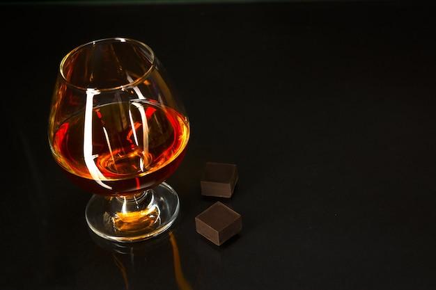 Weinbrandglas und -schokolade auf schwarzem hintergrund Premium Fotos