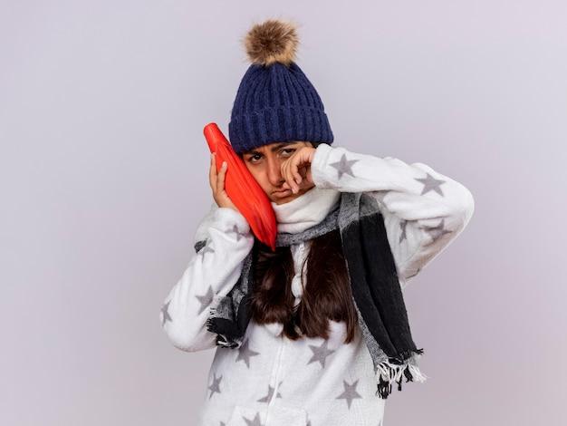 Weinendes junges krankes mädchen, das wintermütze mit schal trägt, der heißen wasserbeutel auf wange setzt und auge abwischt Kostenlose Fotos