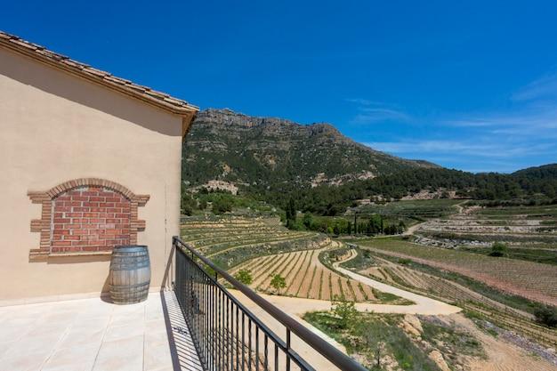 Weinfass auf dem hintergrund des tals der weinberge und der berge Premium Fotos