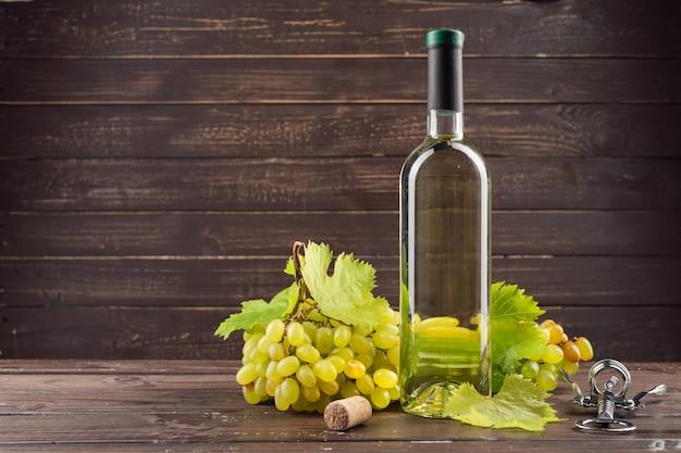 Weinflasche und -traube auf holztisch Premium Fotos
