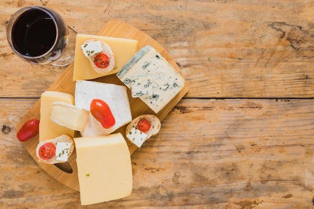 Weingläser mit trauben und vielzahl von käseblöcken auf hölzernem schreibtisch Kostenlose Fotos