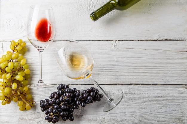 Weingläser, schwarze und grüne trauben, flasche auf weißem holztisch, leerer raum für text Premium Fotos