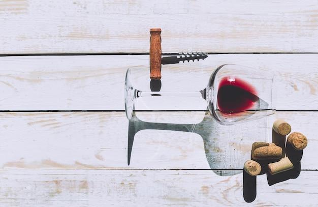Weinglas, korken und korkenzieher über holztisch Premium Fotos