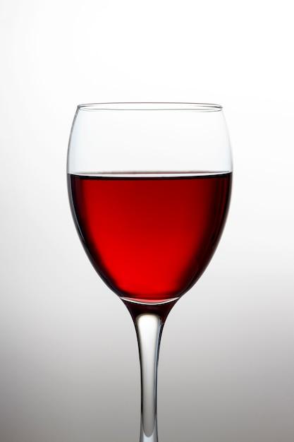 Weinglas mit der rotweinnahaufnahme lokalisiert auf heller steigung Premium Fotos