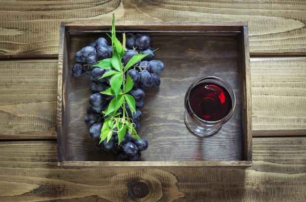 Weinglas mit rotwein und reifer traube auf hölzernem brett. Premium Fotos