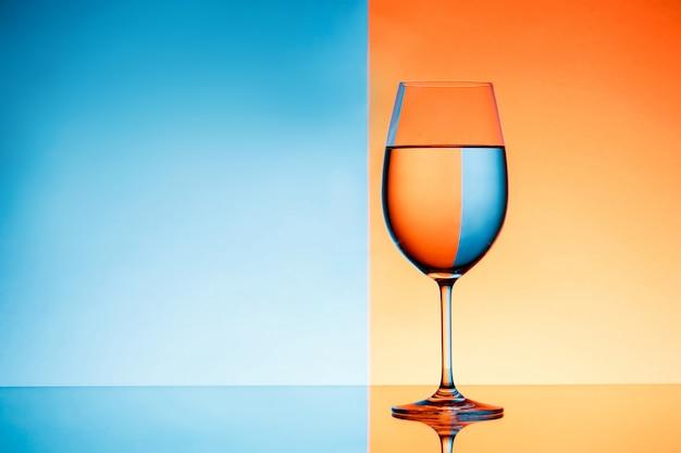 Weinglas mit wasser über blauem und orange hintergrund. Kostenlose Fotos