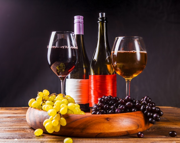 Weinglas mit wein, trauben schwarz, grün auf holztablett auf tisch Premium Fotos
