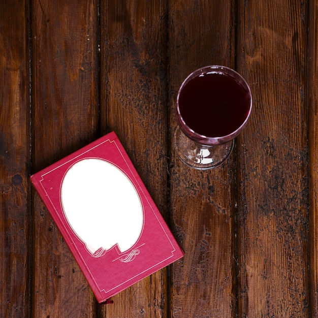 Weinglas und buch auf altem holz Kostenlose Fotos