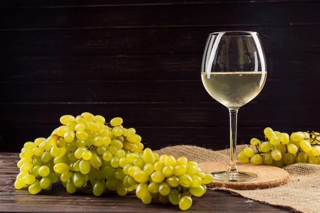 Weinglas und weintraube auf holztisch Premium Fotos