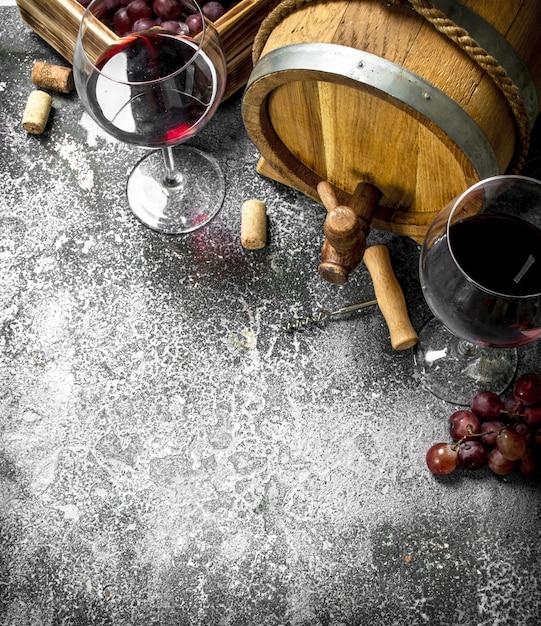 Weinhintergrund. ein fass mit rotwein und frischen trauben. auf einem rustikalen hintergrund. Premium Fotos