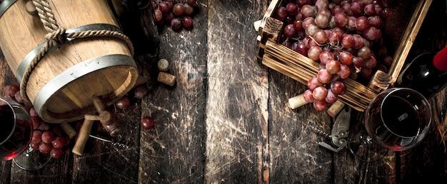 Weinhintergrund. ein fass mit rotwein und frischen trauben. Premium Fotos