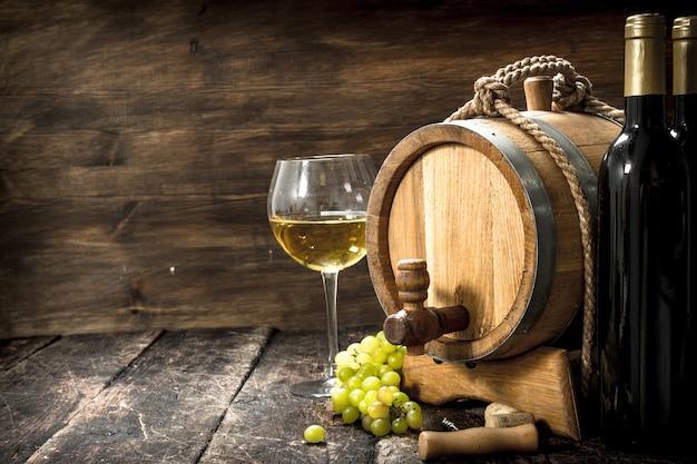 Weinhintergrund. ein fass weißwein mit zweigen grüner trauben. Premium Fotos