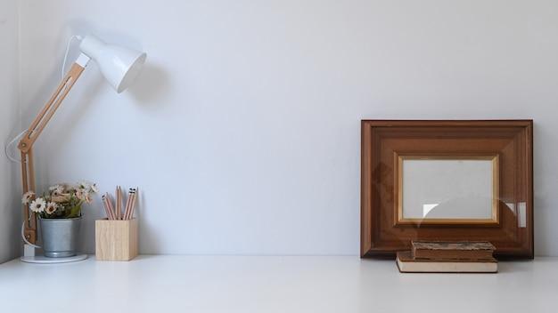 Weinlese-arbeitsbereich mit rahmen, stiften, topfpflanze, kaffeetasse, lampe und altem buch auf weißem tisch. Premium Fotos