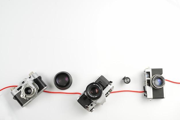 Weinlese der fotografischen ausrüstung, arbeitsplatzkonzept mit grünem blatt auf weißem hintergrund. Premium Fotos