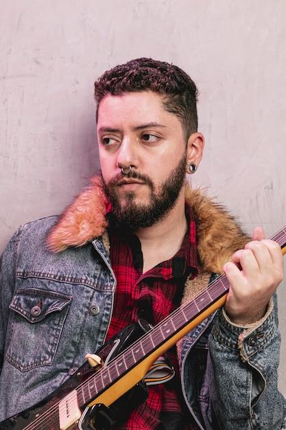 Weinlese gekleideter rocker, der e-gitarre spielt Kostenlose Fotos