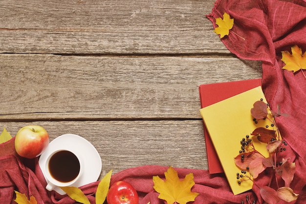 Weinlese-herbsttabelle mit äpfeln, gefallenen blättern, tasse kaffee oder tee auf altem holztischhintergrund Premium Fotos