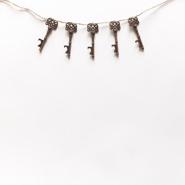 Weinlese-schlüssel, die am weißen hintergrund hängen Kostenlose Fotos