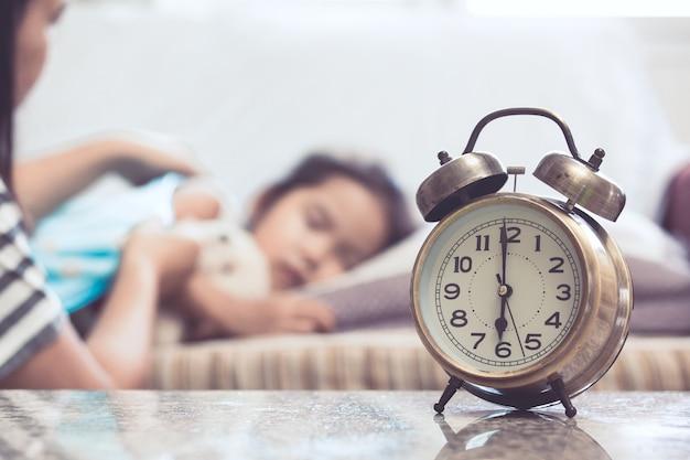 Weinlesealarmuhr auf dem hintergrund der mutter passendes asiatisches kindermädchen, während sie im bett schläft Premium Fotos