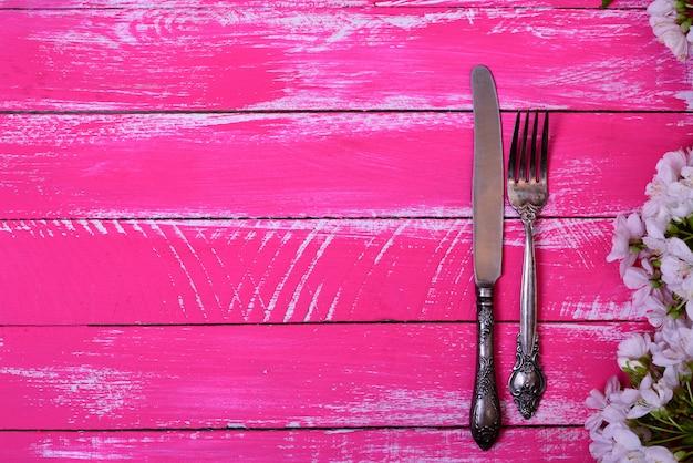 Weinlesegabel und -messer auf einer rosa holzoberfläche Premium Fotos