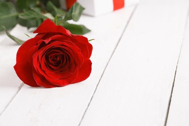 Weinleseoberfläche mit reizender rosenblume auf holztisch Premium Fotos