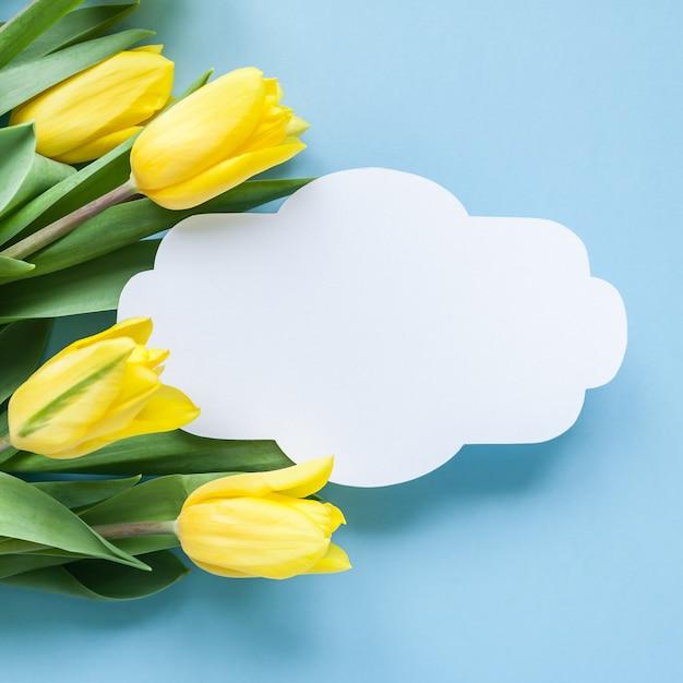 Weinleserahmen und gelbe tulpen auf blauem hintergrund Premium Fotos
