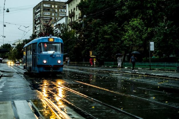 Weinlesestadttram, der in die straße während des regens am abend sich bewegt Premium Fotos