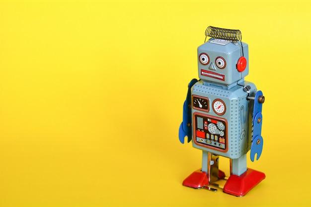 Weinlesezinn-spielzeugroboter lokalisiert auf einem gelben hintergrund Premium Fotos
