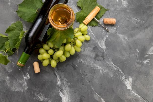 Weintraube mit flasche wein auf marmorhintergrund Kostenlose Fotos
