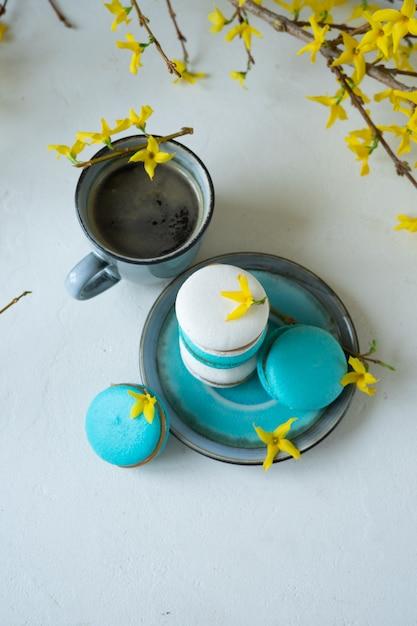 Weiß- und türkismakronen und -tasse kaffee auf weißem hintergrund. gelbe frühlingsblumen Premium Fotos