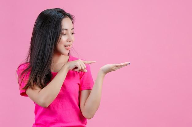 Weiße asiatische frau die rechte hand zeigte auf die linke hand, die die rechte hand hielt. auf einem rosa. Kostenlose Fotos