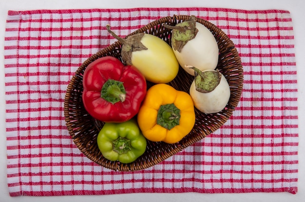 Weiße aubergine der draufsicht mit farbigen paprikaschoten in einem korb auf einem rot karierten handtuch Kostenlose Fotos