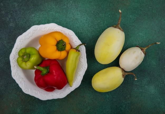 Weiße aubergine der draufsicht mit paprika auf einem teller auf grünem hintergrund Kostenlose Fotos