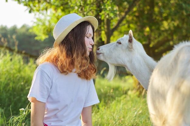 Weiße bauernziege, die teenager-mädchen küsst Premium Fotos