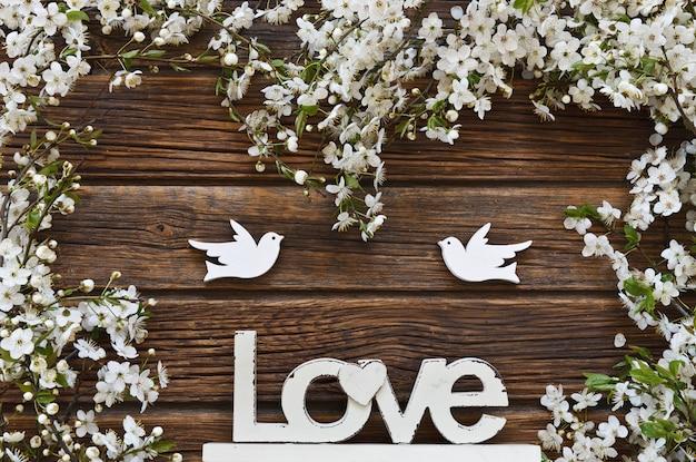 Weiße blühende kirschbaumzweige mit zwei hölzernen vögeln und buchstaben lieben. Premium Fotos