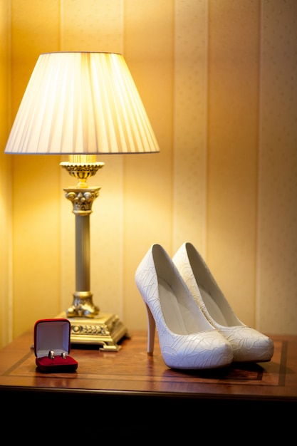 Weiße brautschuhe stehen neben einer roten schachtel mit goldenen eheringen Premium Fotos