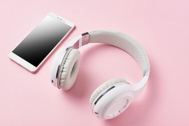 Weiße drahtlose kopfhörer und smartphone auf pastellrosa Premium Fotos