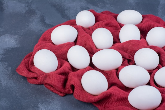 Weiße eier isoliert auf einem stück roter tischdecke Kostenlose Fotos