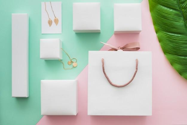 Weiße einkaufstasche- und juwelgeschenkboxen auf farbigem hintergrund Kostenlose Fotos