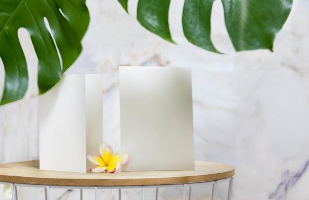 Weiße einladungskarte und blühende plumeria-blume. Kostenlose Fotos