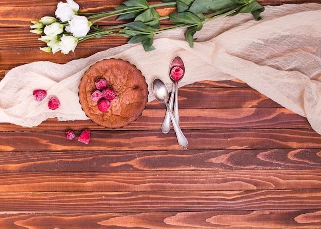 Weiße eustoma-blüten; gebacken mit himbeer-toppings und löffel auf tuch über der holzoberfläche gebacken Kostenlose Fotos