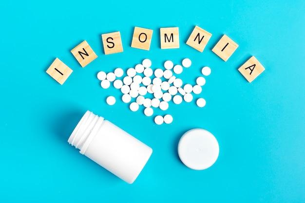 Weiße flasche und pillen auf einem blauen hintergrund. das konzept der behandlung von schlaflosigkeit. Premium Fotos