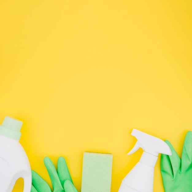 Weiße flaschen mit grünen handschuhen und schwamm auf gelbem hintergrund Kostenlose Fotos