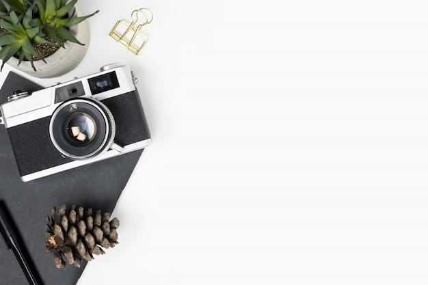 Weiße fotografschreibtischtabelle mit filmkamera und büroartikel. draufsicht mit kopienraum, flache lage. Premium Fotos