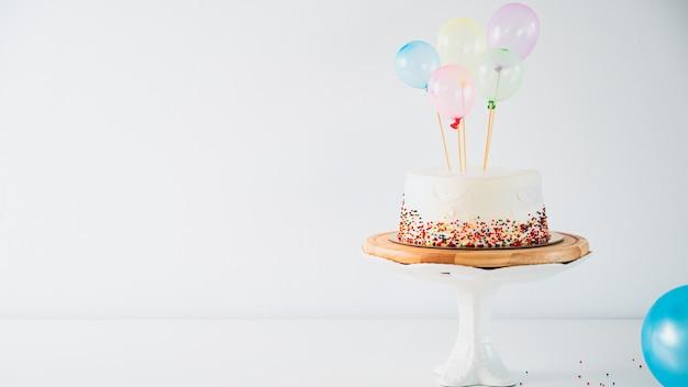 Weiße geburtstagstorte und bunte luftballons über hellgrau.food konzeptjubiläum. Premium Fotos